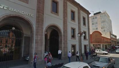 Persona camina a las afueras de una institución bancaria este 30 de marzo de 2020. Foto María Luisa Severiano